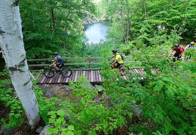Bikers from a summer wrestling camp being held at Spaulding High School cross a bridge at Millstone Trails in Barre Town on Friday. From left are Cameron Govea, who will be a sophomore wrestler at Spaulding, Pat O'Meara, of East Orange, Rob Hamlin who attended Mount Mansfield Union and was a two-time All-American wrestler at Lehigh University, and Spaulding wrestling coach Darren O'Meara.