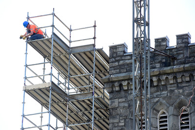 A worker installs scaffolding Friday as repairs to the Christ Episcopal Church towers in Montpelier gets underway.