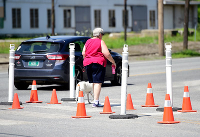 A pedestrian passes a temporary island while crossing Seminary Street in Barre at the intersection with North Main Street on Thursday. The city is testing ideas to make some intersections around the city safer.