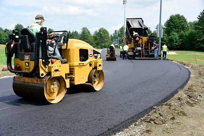 Workers from S.T. Paving apply a coat of asphalt Wednesday to the new track at U-32 High School in East Montpelier. The asphalt will be covered in a rubberized surface when the track is complete.