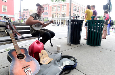 Damon Williams, of New Orleans, plays banjo on a bench Wednesday in downtown Montpelier as he raises money for gas for his return to Louisiana. Williams came to Vermont to check out the Yestermorrow Design/Build School in Waitsfield and visit friends.