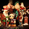 "12-17-2010<br /> ""Checking it Twice""<br /> <br /> After a full day today, I guess that's the way it will be the closer to Christmas Day it gets, I thought,   hmmmmm I need to take a photo.  The first Santas I started collecting were the ones pictured.  Friends and family gave me many through the years.  My favorite place to display them is on my dining room table.  When Christmas is over they go into a cuiro in the dining room.  That being said, I decided this was the photo for today because while Sutton and I were running errands after she got out of school early, she had a notepad and was writing a letter to Santa while I was driving.  She has told everyone, including Santa, what she wants for Christmas but I guess she just wanted to put it in writing.  So I thought this one of Santa reading the list to Mickey Mouse was very appropriate for today.  ( My sister gave this Santa to Tucker to begin his collection of Santas, but what does an 11 year old think of these now?  One day I will pass them on to him and/or his children as great memories of Christmas in our family.) As I looked at the photo I was repeatedly drawn to the eyes of the Santa playing the string bass. It is actually a music box (which I also collect) and it plays ""Santa Claus is Coming to Town.""  I find it rather unique since there is not string bass sound in the music box.  (Sometimes it just doesn't pay to be a musician.)  :)  Okay, back to the eyes, they look so intense in the music he is playing.  I just love his face.<br /> <br /> Thanks for all of the comments on my ""Ten Lords A-Leaping.""  If you knew the personalities of the boys in that shot you would really be laughing.  They were having so much fun, and always do.<br /> <br /> Side note----- Yes my dining room walls are black and it has a gold ceiling.  I guess you just have to be here!  I always get a lot of comments on my decor.  Now before you freak out, it is a soft beige below the chair rail which you cannot see in this photo.  Unlike so many these days, I do have a formal dining and living room!  I love it!  <br /> <br /> Have a very happy weekend!  Santa comes one week from today!!! I can't wait!<br /> Donna"