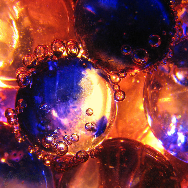 "01/09/10 - Alternate Realities<br /> I cleaned this up yesterday.  This is the actual shot of the marbles with the red sparkling grape juice vs. the apple yellowish cider from last week.  This time I used the smaller blue marbles like last week but also had some slightly larger and normal size peach colored marblesin the mix.  OI guess it turned out kindof other worldly looking.  <br /> <br /> I played with a blacklight last night with the same marbles, grape juice flat from sitting for a day, and this was the result:<br />  <a href=""http://fotomom.smugmug.com/Art/Glass-Appeal-28/10887163_feHdr#760439399_t3jdS"">http://fotomom.smugmug.com/Art/Glass-Appeal-28/10887163_feHdr#760439399_t3jdS</a><br /> Now, how did I make it glow in the dark you ask? I added tonic water in with the grape juice.  Tonic water contains a chemical that is flurescent:-)  And, while I shot with the blacklight, the boys created this scene to test things in the house to see what would and would not glow:<br />  <a href=""http://fotomom.smugmug.com/Art/Glass-Appeal-28/10887163_feHdr#760439399_t3jdS"">http://fotomom.smugmug.com/Art/Glass-Appeal-28/10887163_feHdr#760439399_t3jdS</a><br /> Fun stuff!<br /> <br /> Thank you all so much for your commets on my bubble shot from yesterday.........  <br /> <br /> HAGD,<br /> Maryann"
