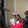 12/24/09 - Caroling<br /> Joey and Madi had both expressed an interest with me in going caroling.  Last year we just didn't make it, so I was determined not to let this year slip by.  I called a few neighbors that I thought would be receptive to give them a heads up that we'd be coming around, and they were happy to have the kids stop by.  I printed out the first verse of several well known Christmas songs like Silent Night, Jingle Bells, and We Wish You a Merry Christmas too.  <br /> <br /> Here the kids are singing for Bill and Jeanne.  I wish more of Jeanne was in the picture, but I love the smile we can see on Bill's face.  <br /> <br /> The kids came away with cookies from most of the houes (5).  Next year I'll try to include more kids and more houses, but this was a great first year outting.  <br /> <br /> Johnny was with us, but although he knows many of the lyrics, he was more interested in socializing and checking out people's houses than singing the songs.  Maybe next year too.<br /> <br /> Glad you got a kick out of Santa Cow:-)  Thank you...<br /> <br /> It's almost time to call Christmas shopping 2009 a wrap...<br /> <br /> Stay safe if you're traveling and HAGD,<br /> Maryann