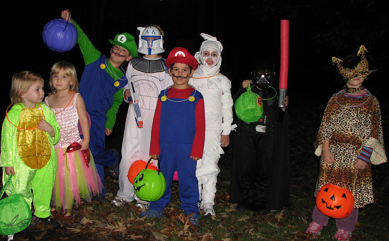 """11/1/09 - Trick-Or-Treat!<br /> Here are the kids that made my Halloween so special this year.  From left to right is Sophie, Sienna, Joey, Grayson, Johnny, Madi, Eli, and Celeste.  Sienna's baby sister Mira is not pictured, but otherwise, this is 5 households of kids.  A great bunch, and they had a great time as did us parents walking with them.  75 degrees at dark.  We were SO hot!  <br /> <br /> If you'd like to see a picture of the haunted garage, go here:<br /> <br /> <a href=""""http://fotomom.smugmug.com/Children/Halloween-Fun-2009/9845761_KK5Lt#699269432_Fnfhj"""">http://fotomom.smugmug.com/Children/Halloween-Fun-2009/9845761_KK5Lt#699269432_Fnfhj</a><br /> It was a big hit with all the kids...spooky but not too spooky;-)<br /> <br /> Rain here...AGAIN.  So much for a hike in the woods today:-(  Too wet to put up the outdoor decorations too.  Beats a work day though!!!<br /> <br /> HAGD,<br /> Maryann"""