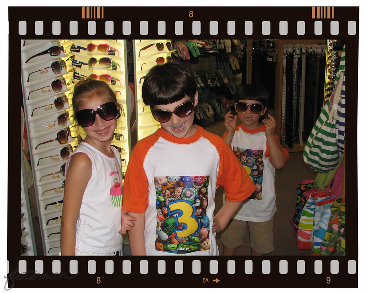 "06/20/10 - Future Hollywood Stars?<br /> Probably not, but they sure where darn cute.  We walked into JCP, I happened to have my camera in it's usual spot around my neck, and in the blink of an eye they had seen the sunglasses display and had a pair on.  I snapped the quick shot and promptly made them put them back.  Just ended up being my favorite shot of the day.  Who can resist those faces.  <br /> <br /> Not to be confused, I had the boys wear their new Toy Story 3 shirts today too.  Kindof a Toy Story 3 weekend.<br /> <br /> I really wanted a Hollywood Clapboard frame, but this filmstrip will have to do because after hunting for one for a while I struck out.  This filmstrip frame is part of PhotoFrame 4.0.<br /> <br /> This is like the cutest must see video ever of the kids on the carousel at the mall in the tea cup.<br /> <br /> <a href=""http://fotomom.smugmug.com/Nature/June-2010/12400102_x8pU2#906752756_XFW9m"">http://fotomom.smugmug.com/Nature/June-2010/12400102_x8pU2#906752756_XFW9m</a><br /> The video of them in the race car and on the jumping thing are cool too.  I suppose some people go to the mall to actually shop, but not usually us.<br /> <br /> Tried to destress yesterday by having a good time with the kids, and it was pretty successful for a while.<br /> <br /> No bug pictures today:-)  Thanks for the comments on yesterday's shot.  I was very bummed to see the pretty flower being eaten, but it was already too late when I got there, and not much stopping nature anyway.<br /> <br /> Off to the beach today for a day trip for Father's Day (2+ hours each way).<br /> <br /> Happy Father's Day to all the fathers out there!<br /> <br /> HAGD,<br /> Maryann"