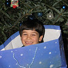 12/20/09 - Hey, that present moves!<br /> Every year around Christmas, Aunt Debbie comes to deliver presents.  Debbie moved into our neighborhood and met our family right around the time Joey was born and has been spoiling the boys ever since.  She has her own grandkids now, but they don't live closeby, and Joey and Johnny still get doted on quite a lot.  Debbie lives about 45 minutes away now, so her stopping by yesterday with goodies was an extra treat.  <br /> <br /> A few years ago, Debbie showed up with the boys' gifts in these big style bags, and the kids did what kids so often do...they paid more attention to the 'box' than the gifts.  As soon as they checked out what was in their bags this year, the immediately hopped into the bags themselves.  You can see the grin!  Joey almost doesn't fit in his bag anymore.  Debbie may have to supersize next year.  But, that didn't stop him from trying.  There was grabbing of the handles and trying to use it like in a sack race too.  Fun stuff!<br /> <br /> Today is the anual kids' Christmas party at our house.  J&J and 9 friends will be having fun starting at 1PM.  Mostly I have the crafts, food, and set-up under control, but I'll be a busy camper for the next few hours making sure things are just right.  <br /> <br /> Thanks for your comments on my crystal Santa and tree from yesterday.  It's amazing what you can do with less than $5 of stuff from the thrift store.  <br /> <br /> HAGD,<br /> Maryann