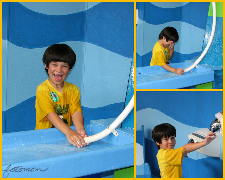 08/03/09 - OK, here's the birthday boy, Johnny, who just turned 5.  And, what is he doing again?  Why playing in water of course!  You may remember that he's mud puddle boy;-)  These pics are also from his b'day party at Marbles Kids Museum.  In yesterday's shot of Joey and the shark, Johnny was standing behind him at the hand dryer.  <br /> <br /> What you can't immediately tell from the picture is that the white pipe has a tiny hole at the bottom of it and when you close off the water flow with your finger you get splashed in the face.  If you look close, well maybe you don't need to look THAT close, you can tell his shirt is soaked:-)  I tried to get a 'spray' picture, but that was truly proving to be bad for my camera's health.  <br /> <br /> Continued thanks for looking and commenting on my pics and for the sense of community here.