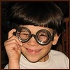 03/08/11 - Johnny and the Magic Glasses<br /> <br /> Unfortunately, I didn't have time to get out and shoot any flower pictures yesterday.  However, Johnny provided me with this cute and funny photo op while he was doing his homework.  The kids got these 'Magic Glasses' Friday night at the Vance Spring Festival and have been enjoying them on and off since.<br /> <br /> I built this in PSE since Picasa doesn't build 'straight' collages past 2 long.  I have the hardest time getting the outer border to show up in the pane on PSE if I alter the size of the original in any way.  Obviously, I cropped these shots square.  It's a 6X18 image.  After getting the center dividers to show up in PSE, I used Picasa to add the outer border under their collage feature (you can collage just one image in grid pattern to add a border).  That probably doesn't make sense, but it is what it is.  Brute force when necessary.  <br /> <br /> Commute day for me...sigh.<br /> <br /> I got a call from the PTA on my cell yesterday asking for Joey.  Huh?  Unbeknownst to us, he w won a raffle basket Friday night too.  It's the spa basket:-)  He put tickets in there because he wanted to win that for his Mom.  Isn't that sweet?!?  I'll pick it up today and see what all is in there.<br /> <br /> Oh, I meant to mention too that I used The Puffer that Art Hill had recommended in one of his posts.  It toned down the pop-up flash very nicely.  There is a huge difference in the shots that I used it on vs. the ones that I did not.  He was blowing bubbles in those early shots, so I won't link you to one, but take my word that they lacked richness of color and had a lot more glare.  The only bad thing is that The Puffer really doesn't fit on my camera, so I have to hold it up there...doable for short photo shoots for sure.  <br /> <br /> HAGD,<br /> Maryann