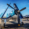 "Vought F4U-1A Corsair...<br /> <br /> HISTORY<br /> <br /> In June 1941, the Navy issued the first production contract for the somewhat revised F4U-1 model and the basic design continued in production until January 1953, at which time over 12,800 Corsairs of all models had been built.<br /> <br /> One of the basically stock Corsairs still active is F4U-1 Bu No .17799 (civil registration NX83782), which belongs to Planes of Fame Air Museum at Chino Airport in Southern California. It first arrived at San Diego, California in August 1943 and was assigned to a Navy fighter squadron (VF84) in the same year.<br /> <br /> In January 1944, the aircraft was reassigned to VBF-14 (a fighter-bomber unit) until being transferred to VBF-98 in February 1945. From the sketchy records available, it appears that this aircraft actually saw combat service in the Pacific with VBF-14 and/or VBF-98. The Corsair was dubbed the ""Whistling Death"" by the Japanese because of the noise that it made in high-speed flight. Between April and June 1945, Planes of Fame's Corsair served with a carrier air support unit (CASU-33) before being withdrawn from active service on August 31, 1945.<br /> <br /> After being sold on the surplus market, 17799 wound up in use as a Hollywood movie prop at the Twentieth Century Fox Studios until it was eventually acquired by Planes of Fame Air Museum in 1970, but did not go on static display at Chino until 1973.<br /> <br /> In 1976, Jim Maloney and Steve Hinton restored the Corsair to flying condition in basically a stock F4U-1 configuration. The primary changes to the aircraft it that it uses a Pratt & Whitney R-2800 engine with a single-stage supercharger from a Douglas A-26 Invader bomber in place of the two-stage, two-speed, supercharged R-2800-8 engine that was more common to the early model Corsair fighters. As a result, the restored Corsair is about 700 lbs. lighter than a stock aircraft, allowing it to have a better rate of climb at low altitudes and a shorter take-off roll.<br /> <br /> DISTINCTION<br /> <br /> Since restoration, the Corsair has taken part in numerous airshows and flown in a variety of Hollywood productions including the Baa Baa Blacksheep television series, Airwolf, Space, an IMAX film and an ABC Wide world of flying video.<br /> Planes of Fame's F4U-1A is currently the oldest airworthy Corsair in the world.<br /> Experienced combat service during WWII. <a href=""http://planesoffame.org/"">http://planesoffame.org/</a><br /> <br /> Planes of Fame Air Show, May 3-4, 2014<br /> Chino Airport<br /> Chino, CA<br /> <br /> Thanks for your views and comments!<br /> <br /> Critiques welcome...<br /> <br /> 21 July 2014"