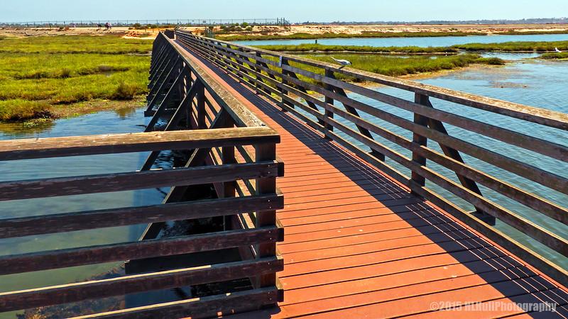 Wooden walking bridge crossing over a tidal inlet,  Bolsa Chica Wetlands...