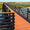 Wooden walking bridge crossing over a tidal inlet,  Bolsa Chica Wetlands...