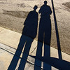 "Late Afternoon Shadows<br /> <br /> My wife and I had gone for a late afternoon walk when I noticed our elongated shadows being cast next to this street sign. I took my camera from my pocket, and ""click!"" A kinda self portrait(s) I suppose!"