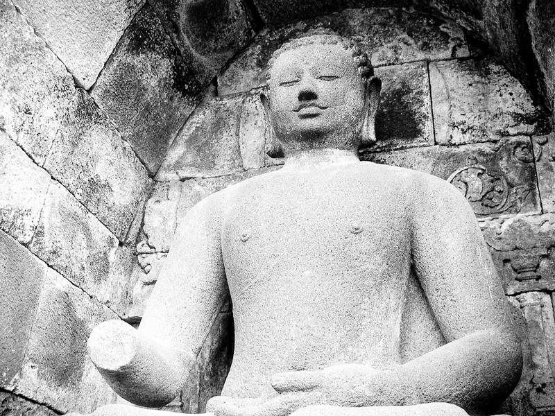 One of the many armless (or headless) Buddha's at Borobudur. Between 1942-1945, when Japan occupied Indonesia, they destroyed many of the stone Buddha's that surround this massive temple.<br /> <br /> (If your interested in seeing more of this temple, check out my 'temples of Asia' galery under 'travel')