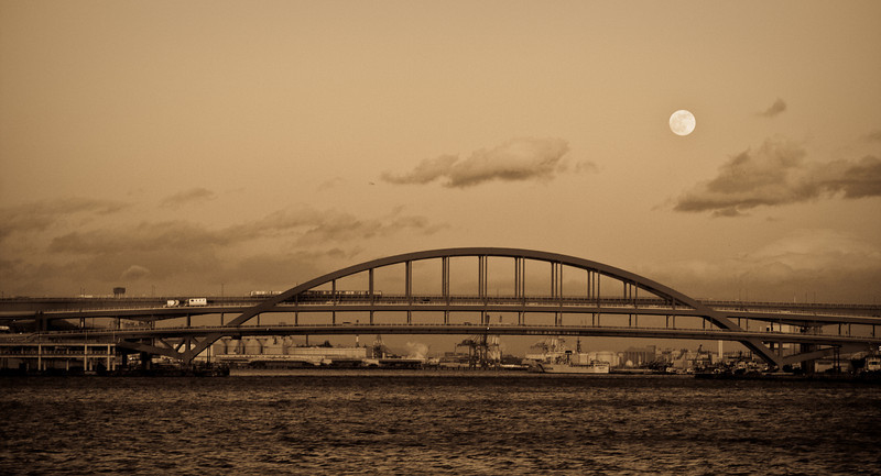 Bridge leading to Kobe airport. <br /> My Aunt and I took a mock pirate ship around the Kobe harbor and watched the sun set on one side of the boat and the moon rising on the other.