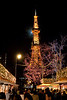 A night shot of Sapporos TV tower taken from the crouded streets of those celebrating Oktoberfest