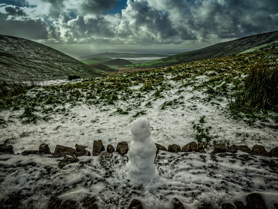 A little snowman admires the view of the Dingle Peninsula