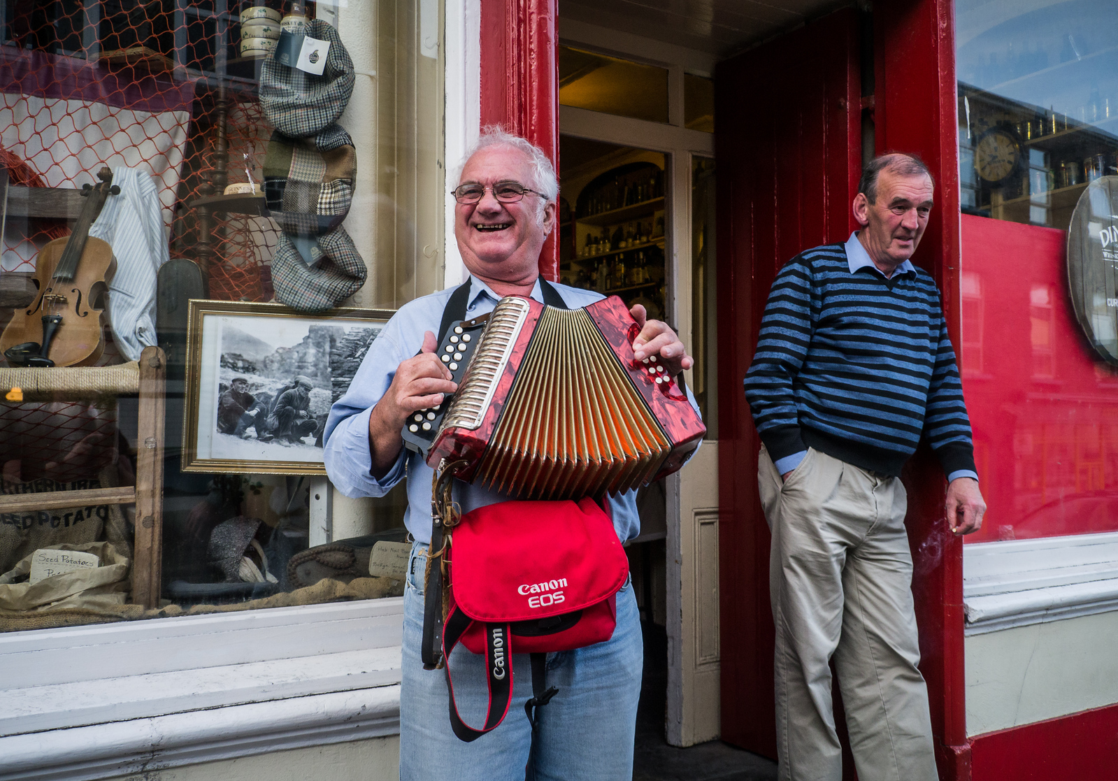 June 21st 2013 An Australian (with a big Canon Eos bag) play the Accordion outside a Dingle pub with a local looking a bit bemused ..