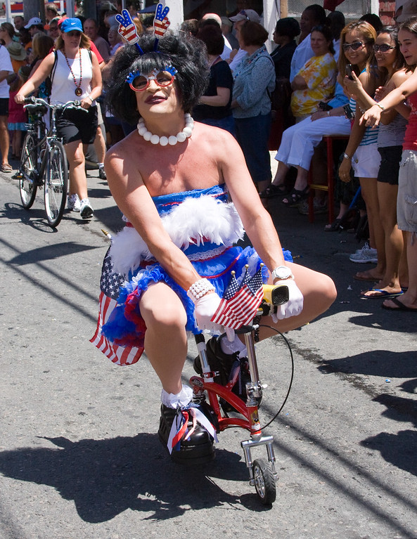 7/6/10  Only in P'town<br /> <br /> In the July 4th parade in Provincetown, this patriotic peddlar entertained the crowds in his/her red, white, and blue.