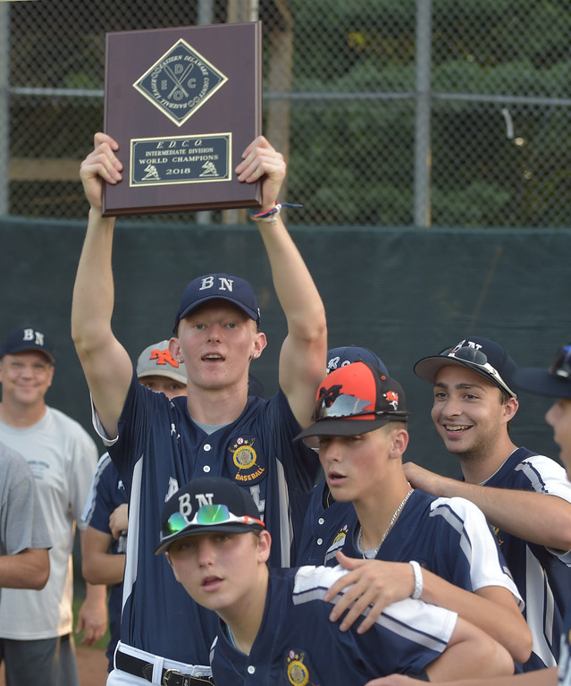 . PETE  BANNAN-DIGITAL FIRST MEDIA         Broomall-Newtown\'s (9) Sean Donnell holds up the EDCO  Intermediate Championship plaque Thursday at Thomas Field in Marple after defeating Springfield two gmes to zero.
