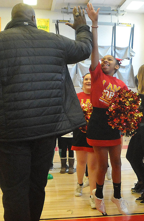 . PETE BANNAN -DIGITAL FIRST MEDIA        Former Eagle and  present NBC analyst Barrett Brooks gives a Haverford Middle School cheerleader a high-five.