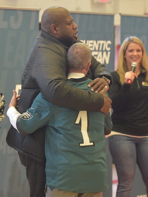 . PETE BANNAN -DIGITAL FIRST MEDIA        Principal Dan Horan was presented a personalized Eagles jersey by Eagles cheerleaders.  Former Eagle, and current NBC analyst Barrett Brooks urged Horan to put the shirt on then gave him a big bear hug to the students joy.