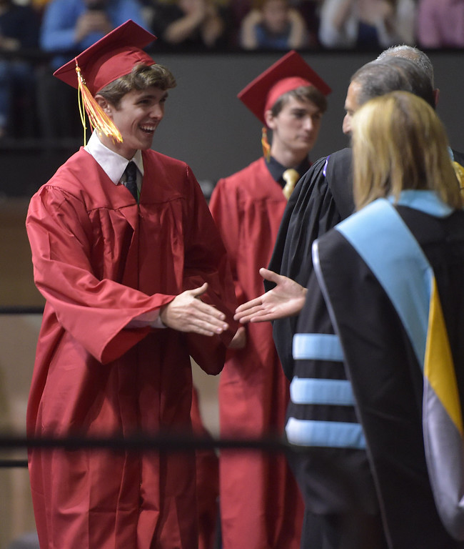 . PETE  BANNAN-DIGITAL FIRST MEDIA        Haverford High School senior Ryan Christopher Millay Millay shakes hands with school board members during commencement exercises at Hagan Arena on the campus of St. Joseph\'s University Thursday evening.