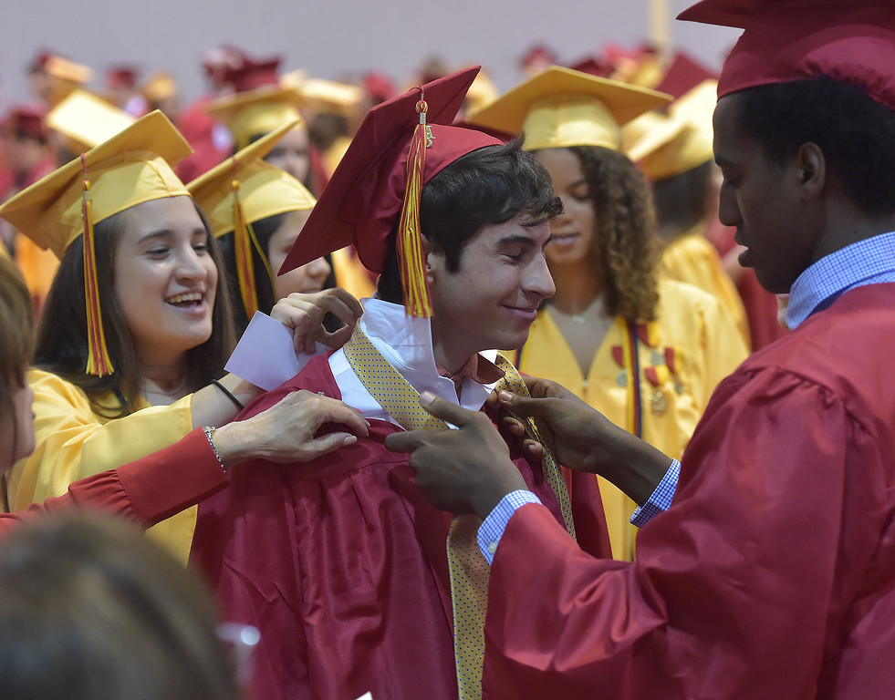 . PETE  BANNAN-DIGITAL FIRST MEDIA      It takes a village, fellow Haverford High School  graduates help Brandon Bonafino get ready for commencement exercises at Hagan Arena on the campus of St. Joseph\'s University Thursday evening.