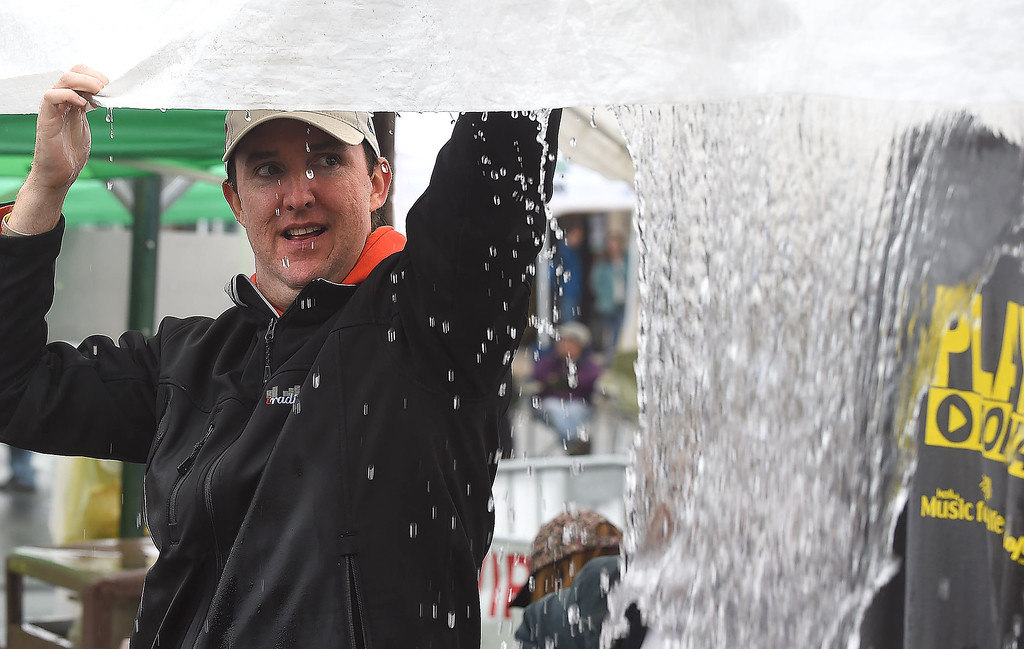 . PETE BANNAN-DIGITAL FIRST MEDIA  Geoff Hazelwood of Iradio Philly pushes water off a tent at the Haverford Spring Music Festival on Sunday May 1 on Brookline Blvd. in Havertown. The rain or shine event  featured six bands including The Verve Pipe and Chico\'s Vibe.