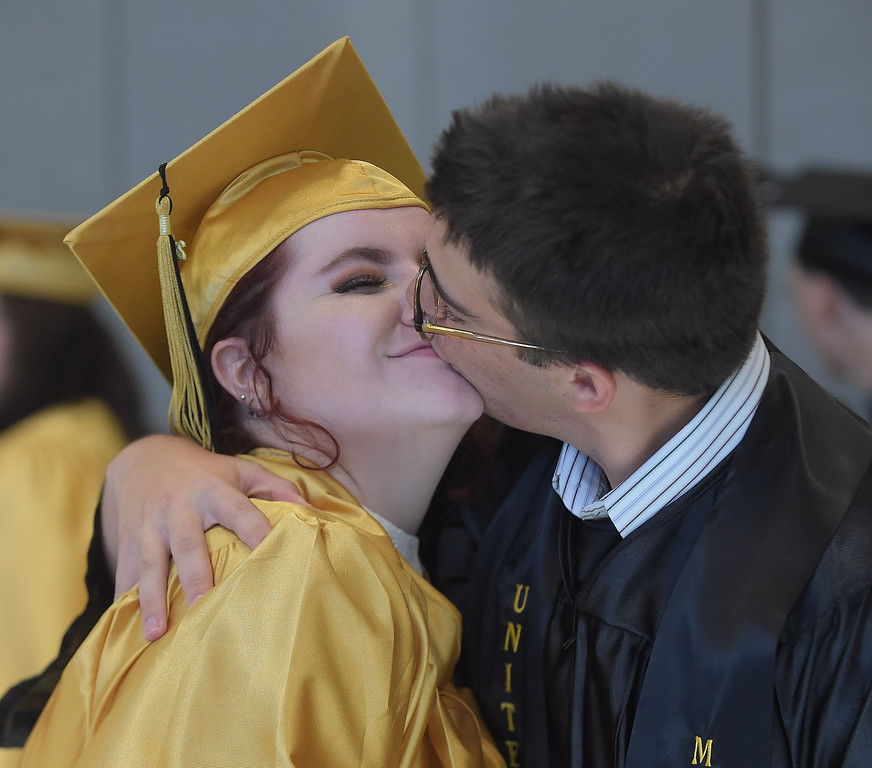 . PETE BANNAN - DIGITAL FIRST MEDIA       Interboro graduate Taylor Sharkey gets a kiss from classmate Dylan Godby commencemt exercises at Neumann University Tuesday evening.  Godby has enlisted in the Marine\'s following graduation.