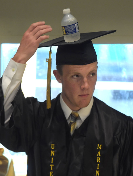 PETE BANNAN - DIGITAL FIRST MEDIA       Interboro graduate Connor McCloskey finds his cap a good  spot to sit his water bottle  while waiting for commencemt exercises at Neumann University Tuesday evening.