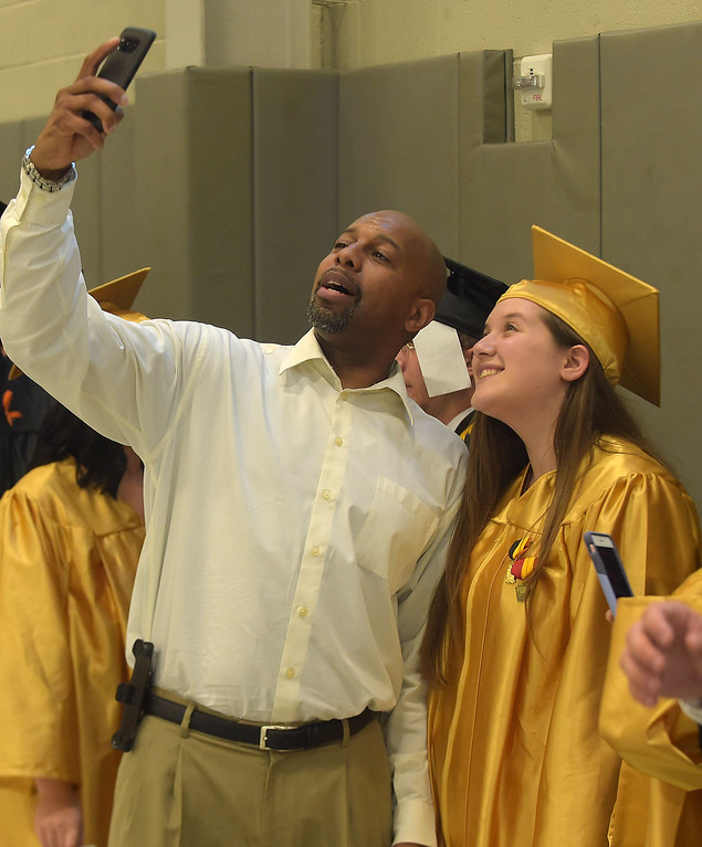 . PETE BANNAN - DIGITAL FIRST MEDIA       Interboro counselor Brian Hines takes a photo with senior Erica DiEmedio prior to commencemt exercises at Neumann University Tuesday evening.