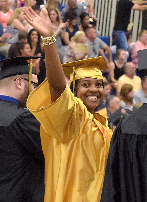 . PETE BANNAN - DIGITAL FIRST MEDIA       Interboro graduate Altrena Campbell waves to family after picking up her diploma at commencemt exercises at Neumann University Tuesday evening.