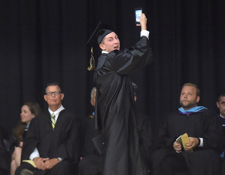 PETE BANNAN - DIGITAL FIRST MEDIA       Interboro graduate Joshua J. Little grabs a selfie while picking up his diploma at commencemt exercises at Neumann University Tuesday evening.