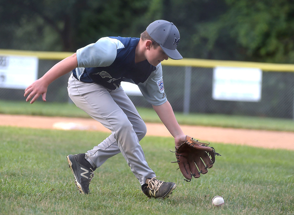 . PETE BANNAN  DIGITAL FIRST MEDIA   Marple pitcher Mike Freeman fields a ball in the fourth inning against Newtown - Edgmont in District 19 Little League tournament action  Wednesday evening at Marple Little League field. Marple won 16-2 and Freeman made the final two outs on fielding plays..