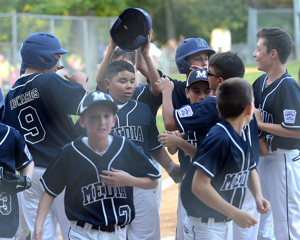 . PETE BANNAN  DIGITAL FIRST MEDIA  Media players surround Mateo Malo , center left, after he hit a grand slam homerun agaisnt South Marple in their 14-1 victory in District 19 Little League playoffs at Aston-Middletown  Monday evening. Jack Edwards,(9) also had a grand slam in the victory.
