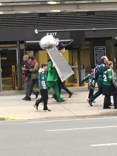 A man carries a large Lombardi Trophy. Photo by Kathleen E. Carey