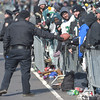 PETE BANNAN-DIGITAL FIRST MEDIA      A police officer returns a football that fans were throwing between the two sides of the parade as they waited.
