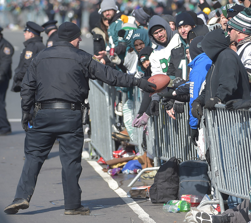 . PETE BANNAN-DIGITAL FIRST MEDIA      A police officer returns a football that fans were throwing between the two sides of the parade as they waited.
