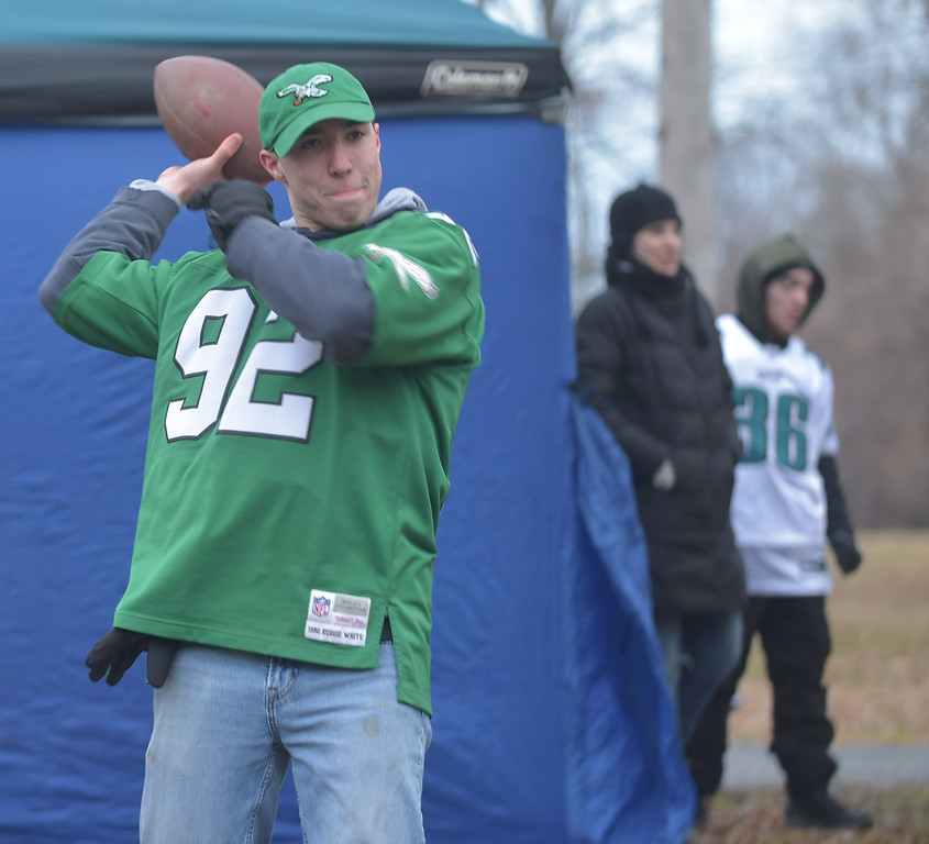 . PETE BANNAN-DIGITAL FIRST MEDIA      Joe Canally of Glenside tosses the football in Fairmont Park Thursday morning after arriving for the Eagles parade.