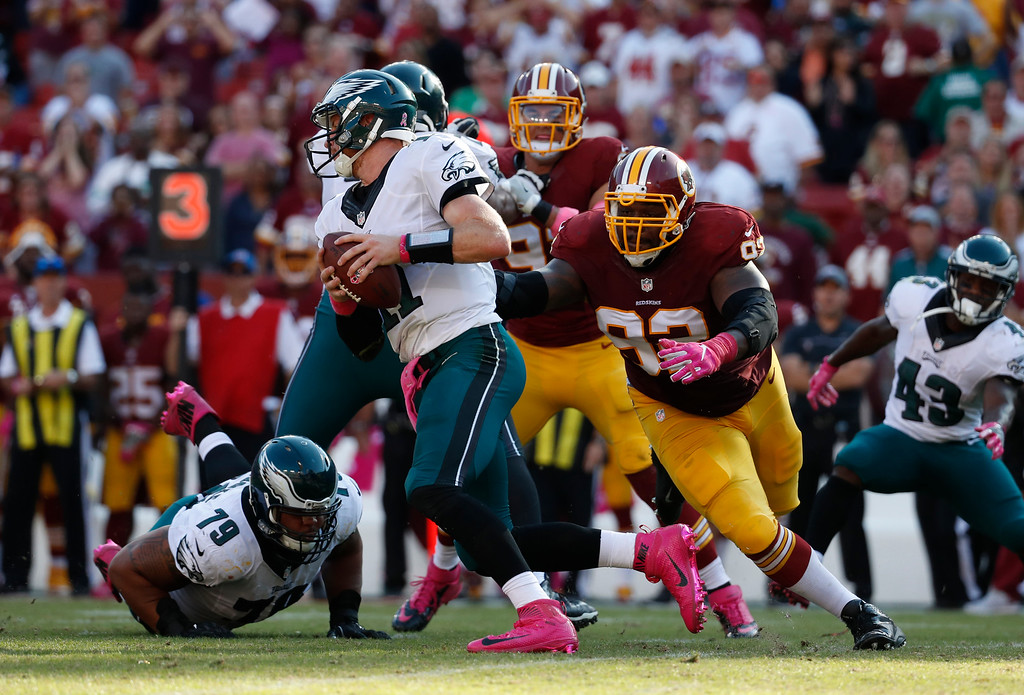 . Philadelphia Eagles quarterback Carson Wentz, center, tries to outrun Washington Redskins defensive end Chris Baker (92) in the second half of an NFL football game, Sunday, Oct. 16, 2016, in Landover, Md. (AP Photo/Alex Brandon)