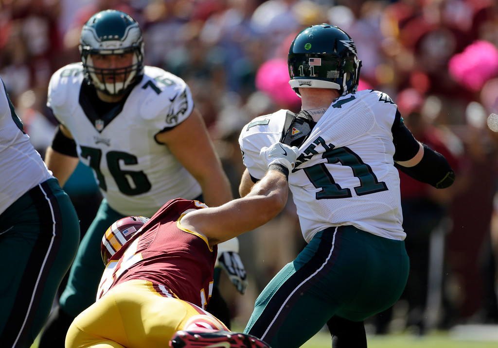 . Philadelphia Eagles quarterback Carson Wentz\'s jersey is ripped by Washington Redskins outside linebacker Ryan Kerrigan in the first half of an NFL football game, Sunday, Oct. 16, 2016, in Landover, Md. (AP Photo/Mark Tenally)
