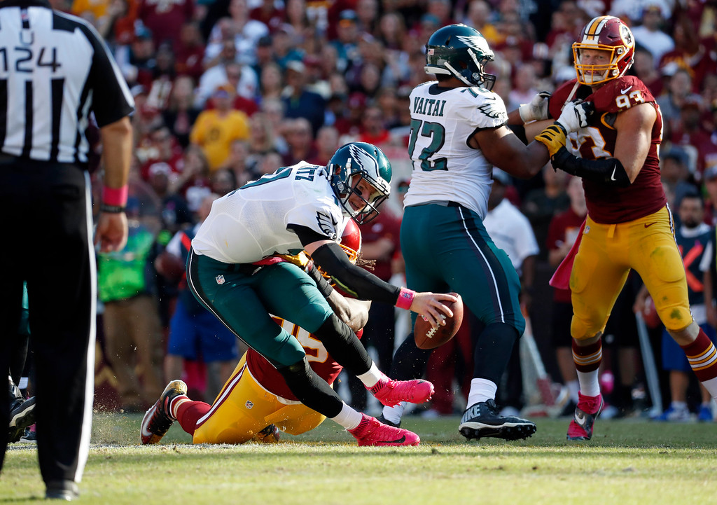 . Philadelphia Eagles quarterback Carson Wentz, left, is sacked by Washington Redskins defensive end Ricky Jean Francois in the second half of an NFL football game, Sunday, Oct. 16, 2016, in Landover, Md. (AP Photo/Alex Brandon)