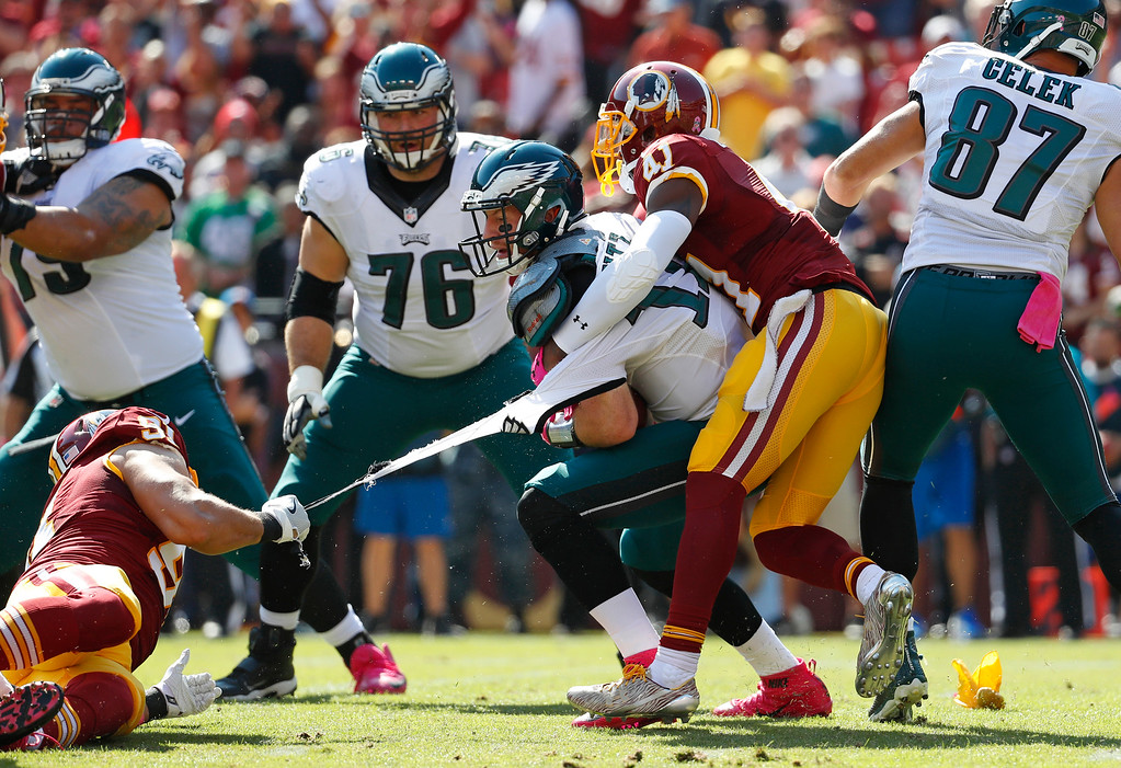 . Philadelphia Eagles quarterback Carson Wentz\'s jersey tears as he is tackled by Washington Redskins outside linebacker Ryan Kerrigan, left, and free safety Will Blackmon in the first half of an NFL football game, Sunday, Oct. 16, 2016, in Landover, Md. (AP Photo/Alex Brandon)