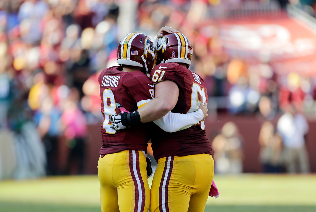 . Washington Redskins quarterback Kirk Cousins, left, and center Spencer Long embrace in the second half of an NFL football game against the Philadelphia Eagles, Sunday, Oct. 16, 2016, in Landover, Md. (AP Photo/Mark Tenally)