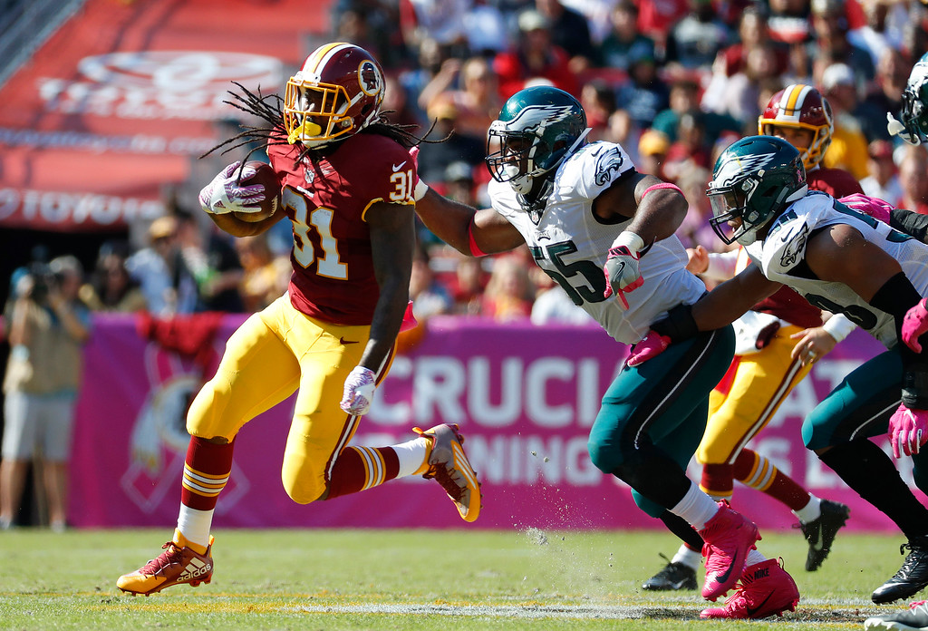 . Washington Redskins running back Matt Jones, left, tries to rush past Philadelphia Eagles defensive end Brandon Graham, center, and linebacker Jordan Hicks in the first half of an NFL football game, Sunday, Oct. 16, 2016, in Landover, Md. (AP Photo/Alex Brandon)