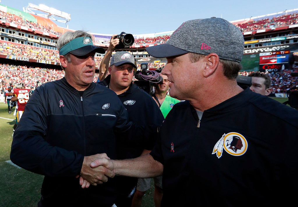 . Philadelphia Eagles head coach Doug Pederson, left, shakes hands with Washington Redskins head coach Jay Gruden after an NFL football game, Sunday, Oct. 16, 2016, in Landover, Md. Washington won 27-20. (AP Photo/Alex Brandon)