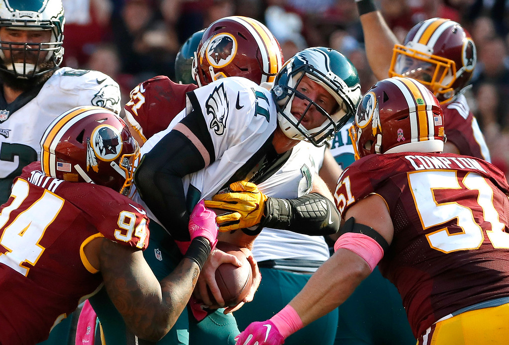 . Philadelphia Eagles quarterback Carson Wentz, center, is sacked in the second half of an NFL football game against the Washington Redskins, Sunday, Oct. 16, 2016, in Landover, Md. Washington won 27-20. (AP Photo/Alex Brandon)