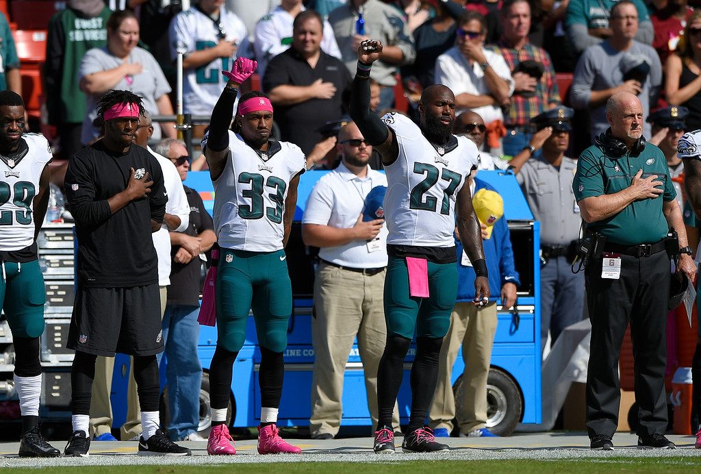 . Philadelphia Eagles cornerback Ron Brooks (33) and strong safety Malcolm Jenkins (27) raise their fists during a rendition of the national anthem before an NFL football game against the Washington Redskins, Sunday, Oct. 16, 2016, in Landover, Md. (AP Photo/Nick Wass)