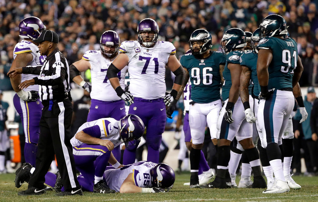 . Minnesota Vikings\' Case Keenum (7) checks on an injured Pat Elflein (65) during the second half of the NFL football NFC championship game against the Philadelphia Eagles Sunday, Jan. 21, 2018, in Philadelphia. (AP Photo/Matt Slocum)